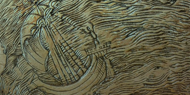 zoomed in etching of a ship with a person at the front