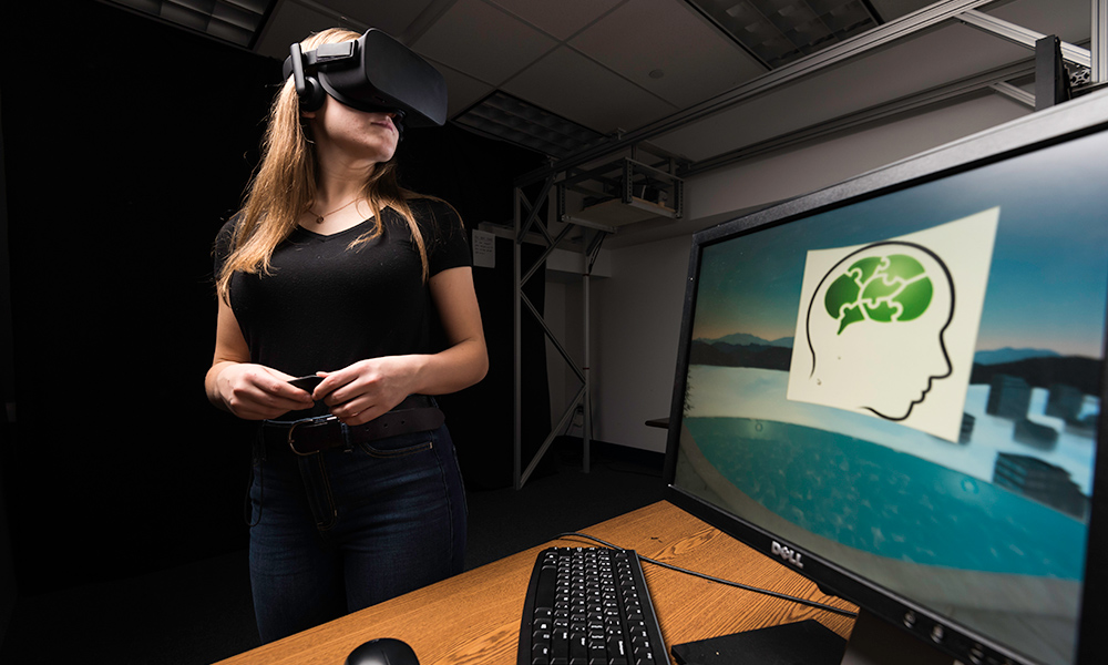 Brenna James '20 wearing a virtual reality headset with a computer in the foreground of the photo