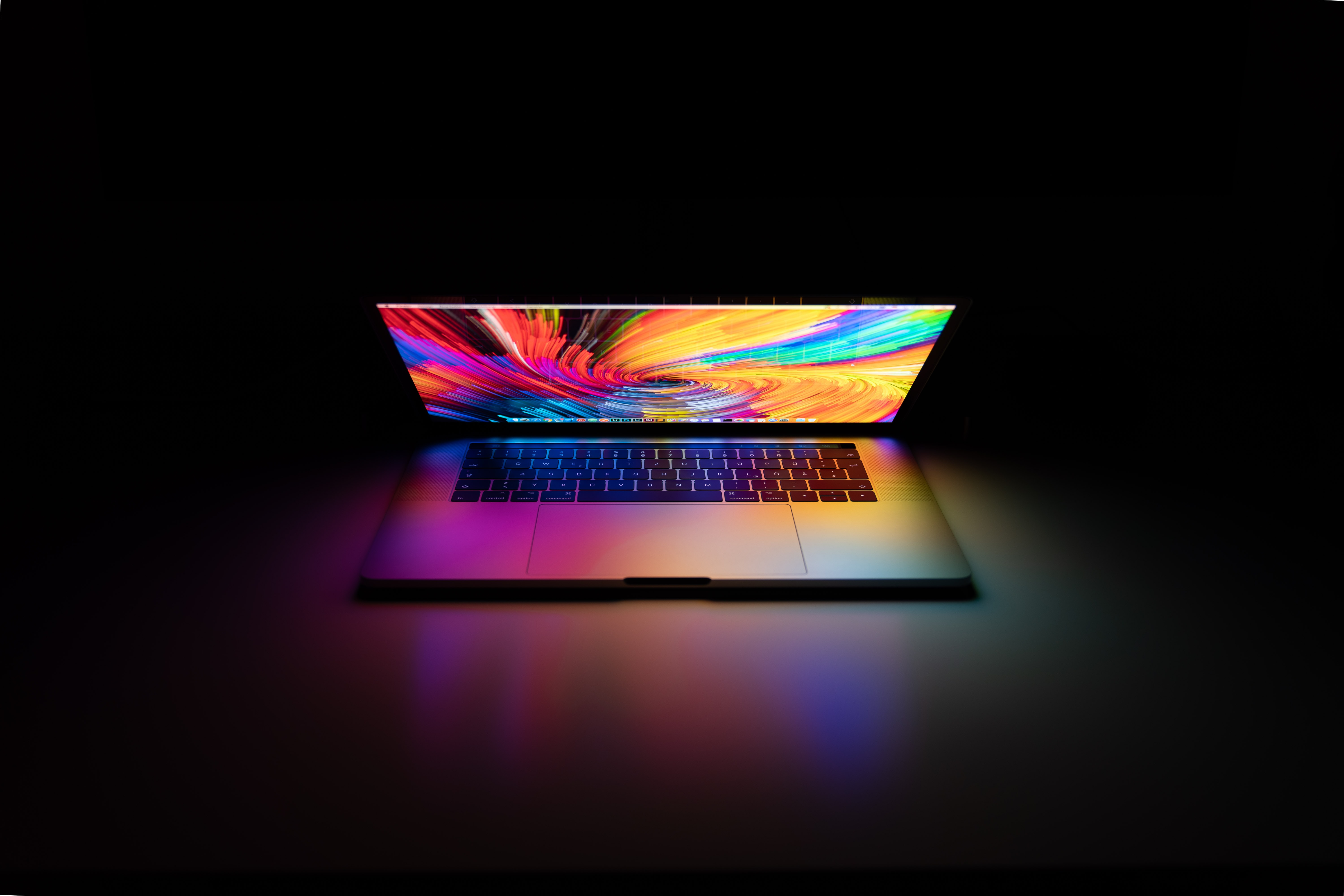 a laptop that is partly open with a colorful screen