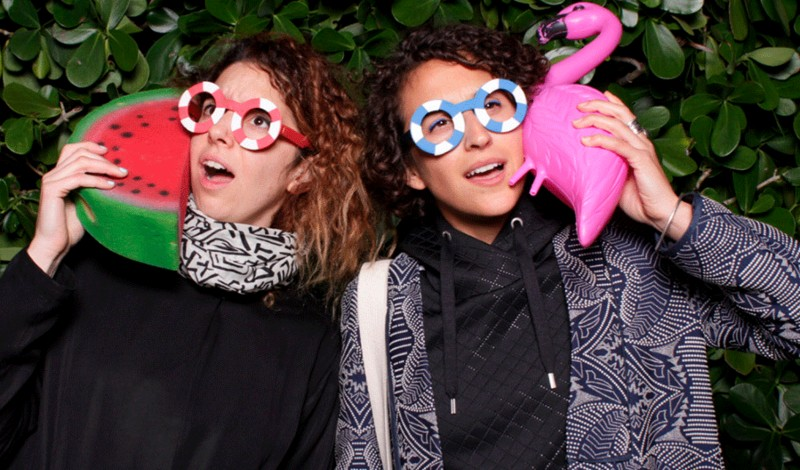 Ece Tankal and Carmen Aguilar y Wedge. They are wearing fun glasses and holding a plastic flamingo and watermelon.
