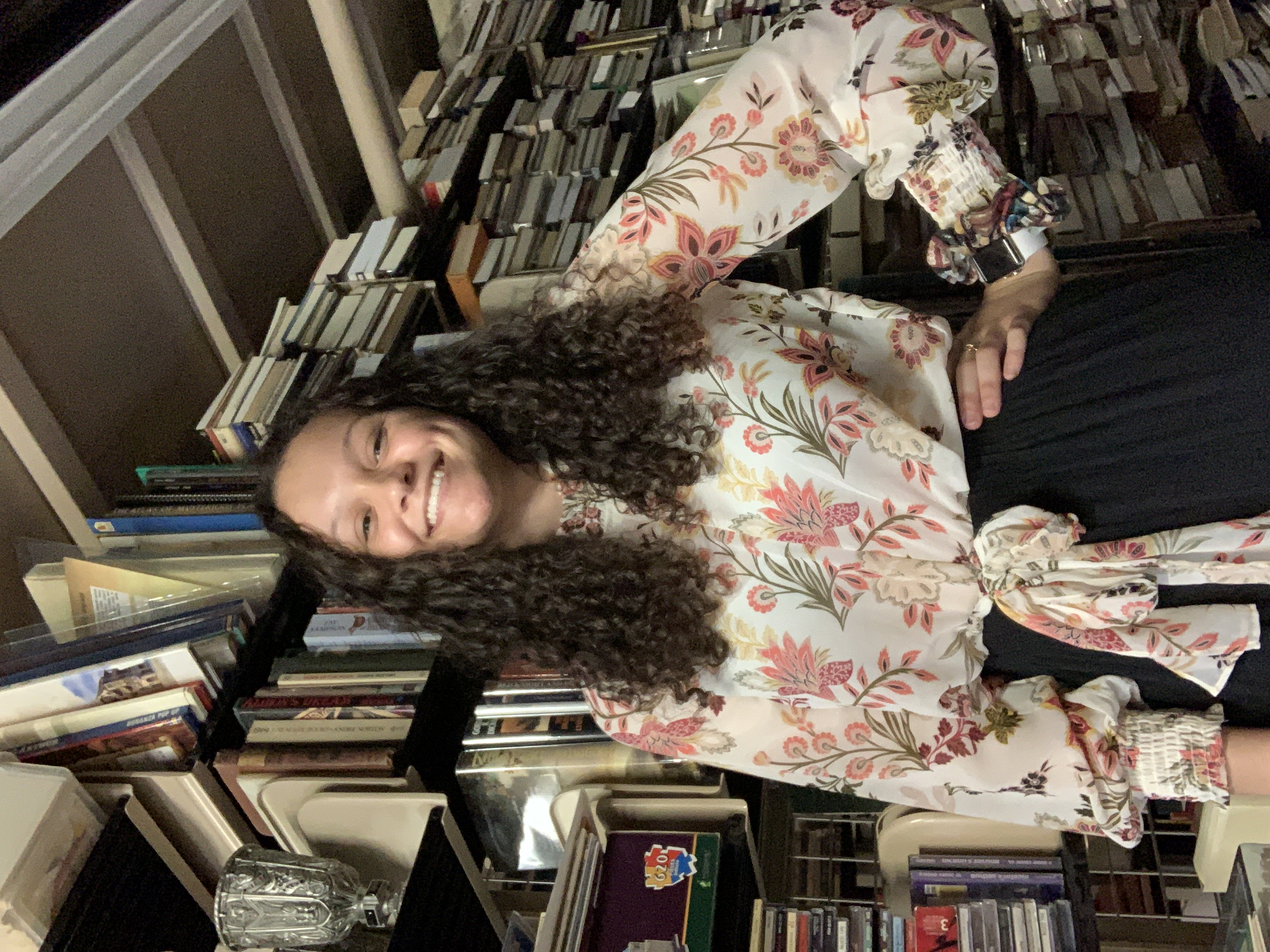 Ayiana Crabtree standing in front of shelves of books.