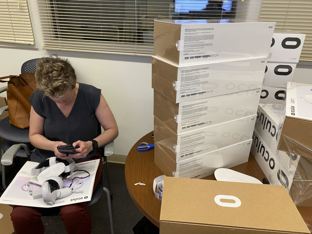 A person working to process a stack of VR headsets.