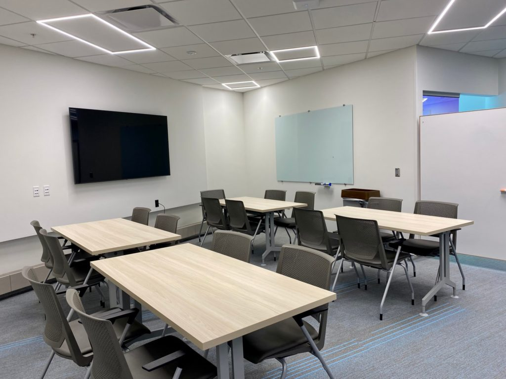Learning Hub. Displays four tables surrounded by chairs and a large wall-mounted TV screen.