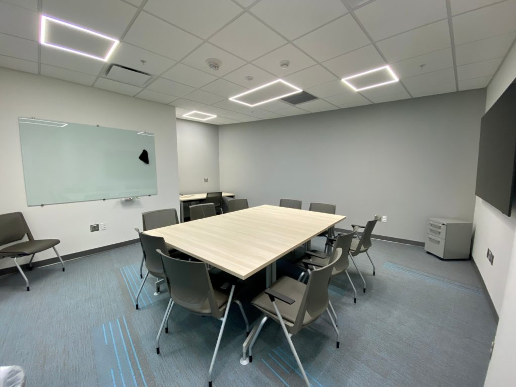 Innovation Suite. Displays a large table with chairs surrounding it. There is a desk in the background.