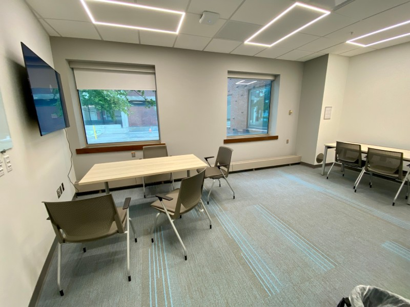 Collaboration Room D. Displays a medium-sized room with a table, windows, desk, monitor, and several chairs.