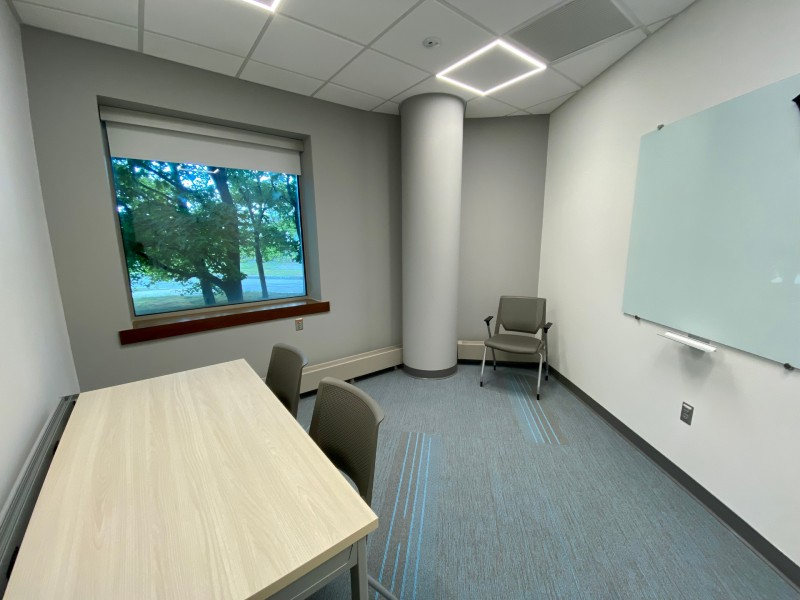 Collaboration Room C. Shows a medium-sized room with a window, a desk, and some chairs.