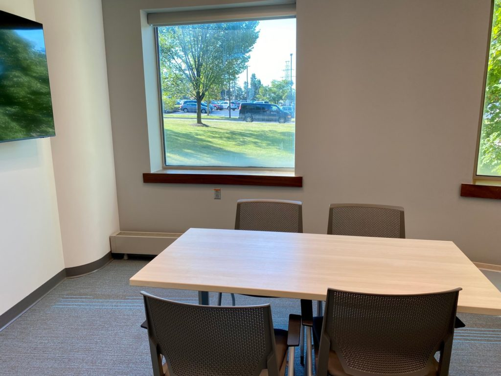 Collaboration room B. Shows a medium-sized room with two windows, a table and chairs, and a wall-mounted monitor.