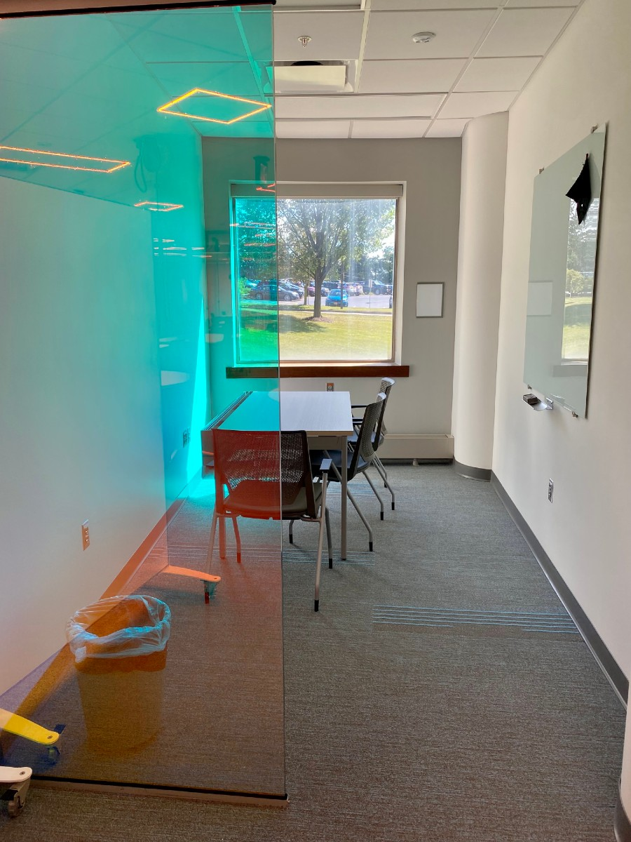 Collaboration Room A. Shows a small room with a desk and a few chairs. There is a window and a glass wall but no full door.