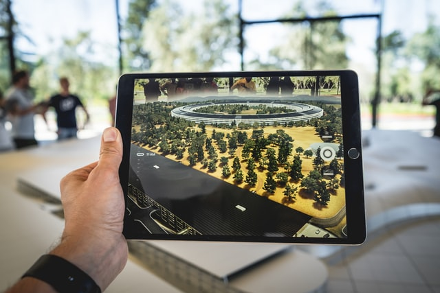 person holding a tablet displaying an augmented reality experience.